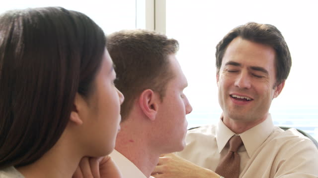 Closeup of young businesspeople in office discussing work