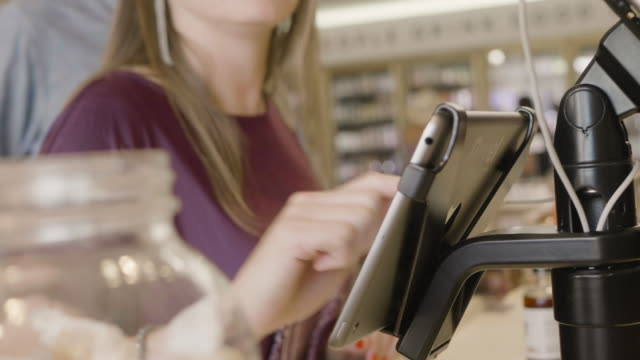 close-up of young caucasian woman's hand as she signs an ipad to complete a credit card purchase at the front counter of a neighborhood market and wine shop. - liquor store stock videos and b-roll footage