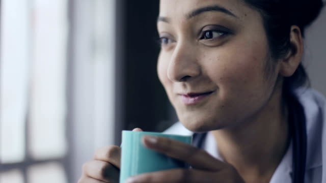 close-up of young female doctor taking coffee break. - lab coat stock videos & royalty-free footage