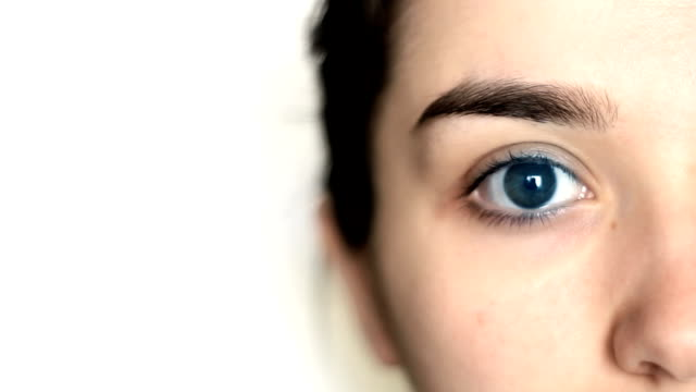 closeup of young female eye - blinking stock videos & royalty-free footage