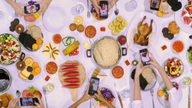 closeup of young friends hands taking photos with their smartphones to food over a table.take candid photo for social media and having lunch in italian food, sausage and salad,big dinner,party - italian food stock videos & royalty-free footage