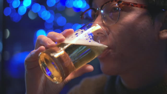 Close-up of young man drinking beer,Slow motion