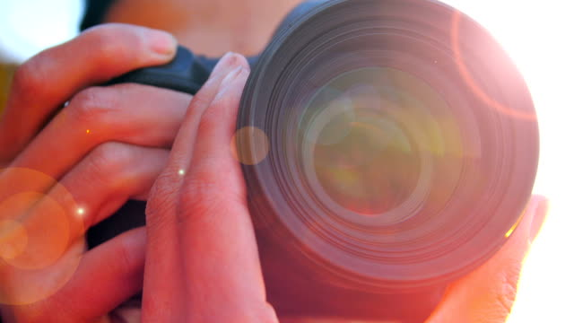 close-up of young man photographing with camera at sunset - photo shoot stock videos & royalty-free footage