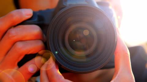 närbild av ung man fotograferar med kameran i solnedgången - fotografi konst och konsthantverksföremål bildbanksvideor och videomaterial från bakom kulisserna