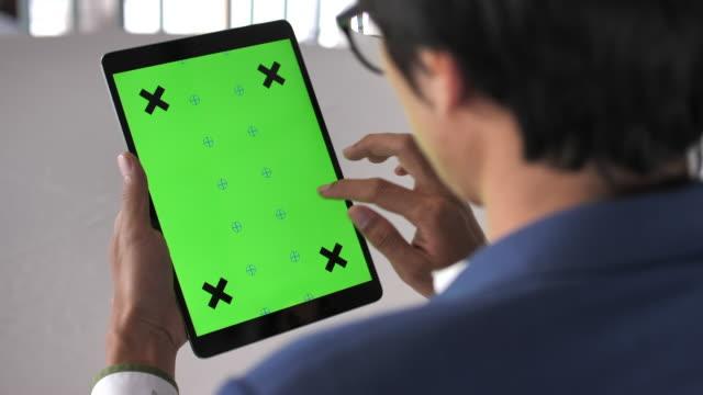 vídeos y material grabado en eventos de stock de primer plano de hombre joven con tableta digital con una pantalla verde - tableta digital