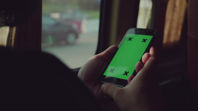 Close-up of young man using smartphone in car,Green screen