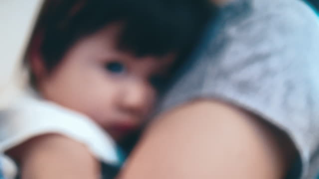 close-up of young mother holding her daughter - stringere tenere video stock e b–roll