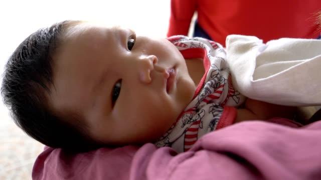 彼女の生まれたばかりの赤ちゃんを保持している若い母親のクローズ アップ - 生後1ヶ月点の映像素材/bロール