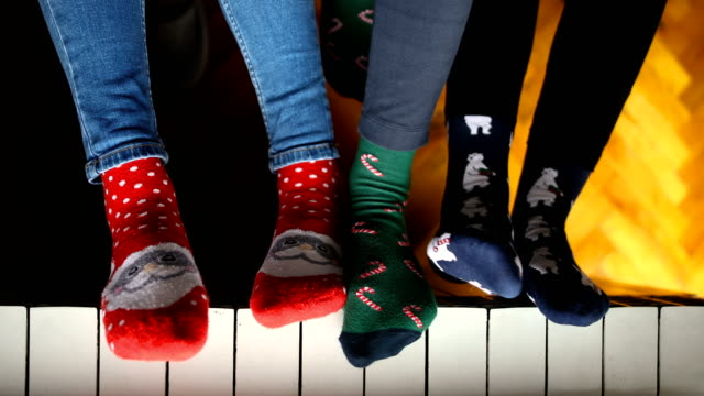 close-up of young people dressed in christmas socks sitting near the radiator - sock stock videos & royalty-free footage