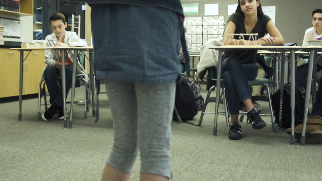 Close-up of young student girl presenting in front of class