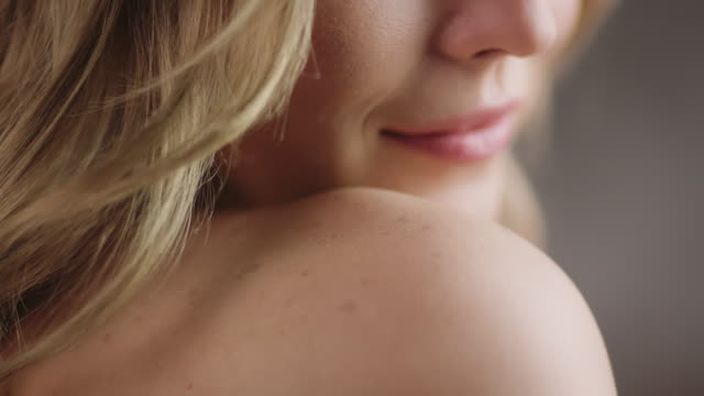 close-up of young woman caressing her shoulder - arto parte del corpo video stock e b–roll