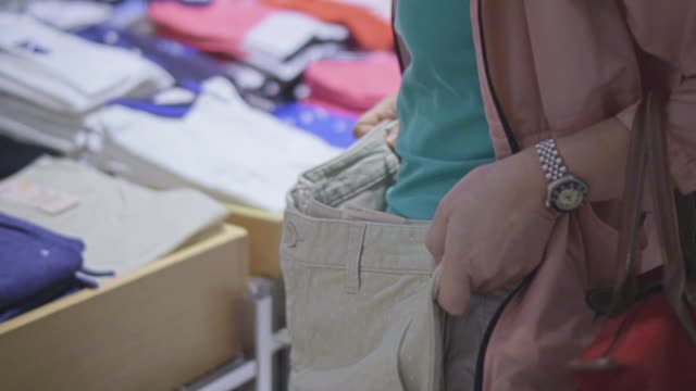close-up of young woman choosing to buy clothes in the shopping mall,slow motion - shorts stock videos & royalty-free footage