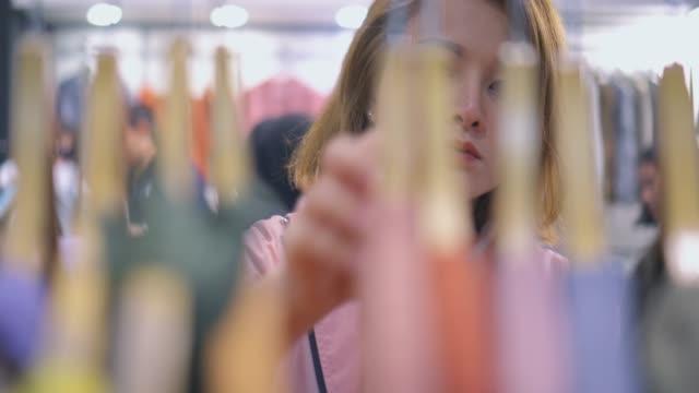 stockvideo's en b-roll-footage met close-up van jonge vrouw op zoek door kleding, slow motion - kledingrek