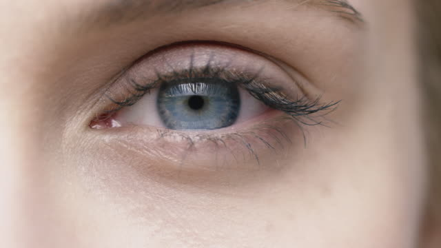 close-up of young woman opening blue eye - eyelid stock videos and b-roll footage