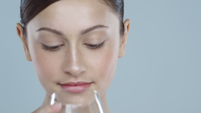 vidéos et rushes de close-up of young woman with glowing skin drinking a glass of water - drinking