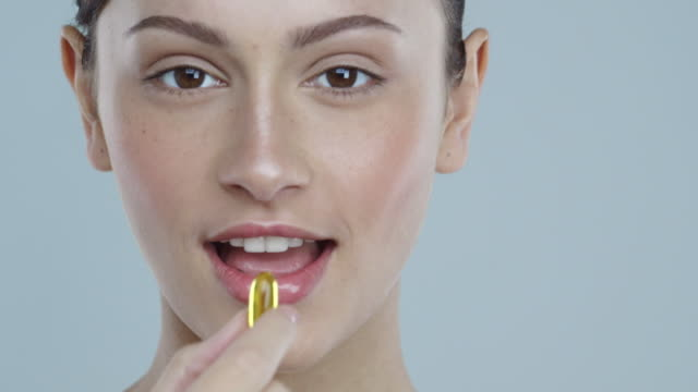 close-up of young woman with glowing skin taking a vitamin pill and smiling - vitamin a nutrient stock videos and b-roll footage