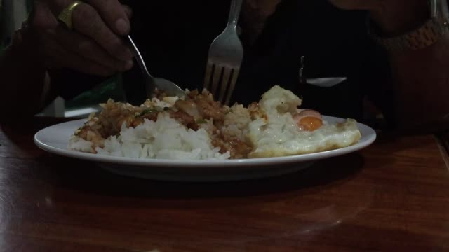 Close-up old man hand eating pork fried with garlic and black peppers and fried egg over steamed rice Thai food