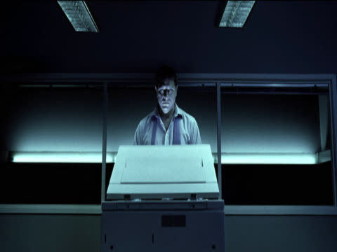 close-up on a bored businessman standing behind a photocopier, the photocopier light illuminating his face - fully unbuttoned stock videos & royalty-free footage