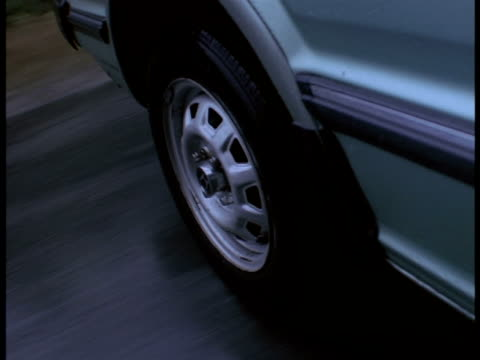 Close-up on a car's tire traveling on wet pavement.