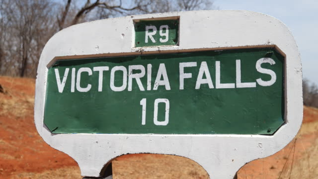 a closeup on a distance sign at the side of the road to victoria falls a large waterfall on the zambezi river at the border of zambia and zimbabwe in... - victoria falls stock videos and b-roll footage