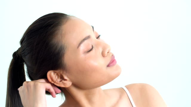 close-up on asian beautiful woman touching on her chin, hair and face on white background. people with beauty, healthcare, emotion concept. - solo una donna giovane video stock e b–roll