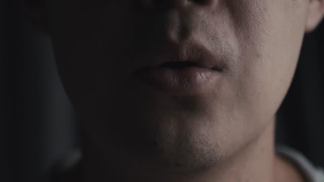 vidéos et rushes de gros plan sur la bouche homme asiatique parler à travers la caméra. concept de communication - lèvres