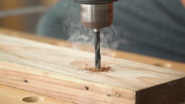 vidéos et rushes de gros plan sur les bits de forage sur la perceuse électrique tout en utilisant pour le forage sur la plaque de bois. il fait chaud jusqu'à ce que la fumée se produise - entretien