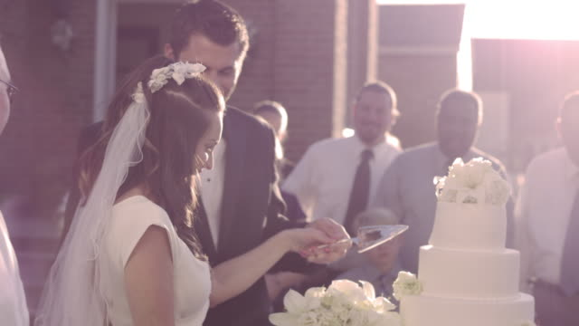 Close-up on hands of a newlywed couple cutting cake.