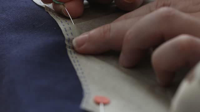 nahaufnahme an den händen, die ein muster in position auf stoff festsetzen - maßkonfektion stock-videos und b-roll-filmmaterial