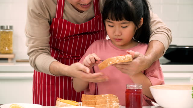 close-up on mid section of father helping daughter putting strawberry jam on bread sheet - strawberry jam stock videos & royalty-free footage