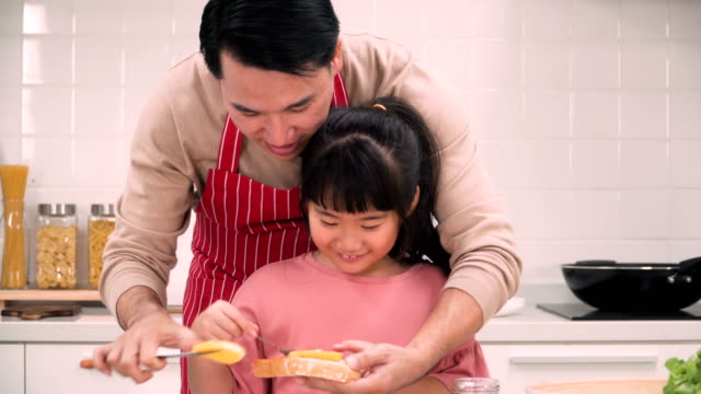 close-up on mid section of father helping daughter putting strawberry jam and other jam on bread sheet - strawberry jam stock videos & royalty-free footage
