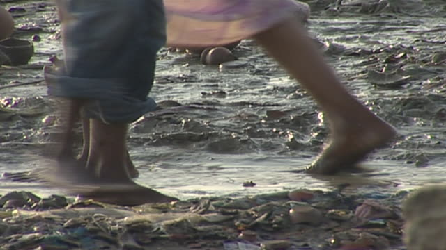 close-up on people's feet as they squelch barefoot in the muddy riverbank in varanasi. - barefoot stock videos & royalty-free footage