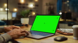 Close-up On the Hands of the Male Specialist Works on a Laptop Computer with Mock-up Green Screen. In the Background Evening in the Stylish Studio Office