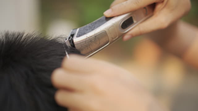 close-up on woman hand cutting hair by clipper at home in covid-19 corona virus situation - razor stock videos & royalty-free footage