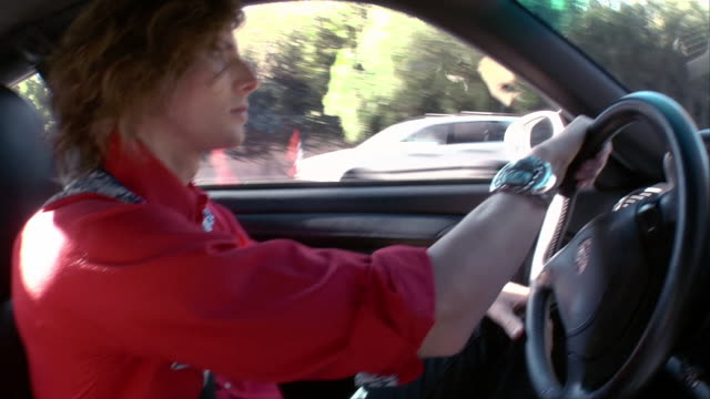 close-up one young man driving car - mid length hair stock videos & royalty-free footage