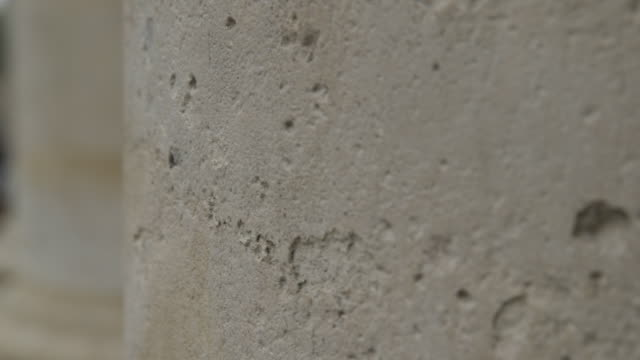 stockvideo's en b-roll-footage met close-up pan across a weathered stone column surrounding a door pocked with ancient fossilised marks, paris, france. - steen rots