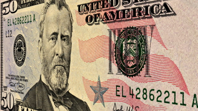 A close-up pan across an American fifty dollar bill.