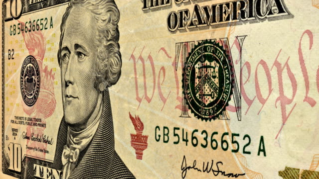 a close-up pan across an american ten dollar bill. - banconota da 10 dollari statunitensi video stock e b–roll