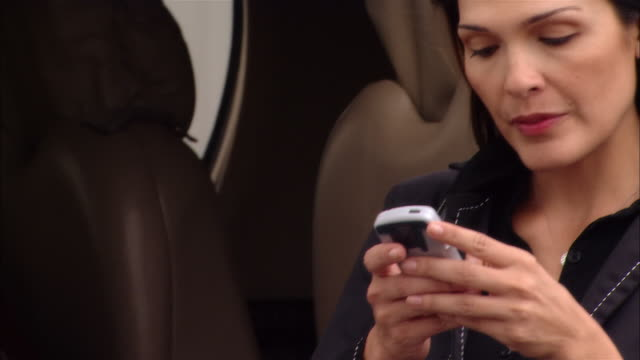 Close-up pan Businesswoman text messaging on mobile phone near private jet at Opa Locka Airport/ Miami, Florida, USA