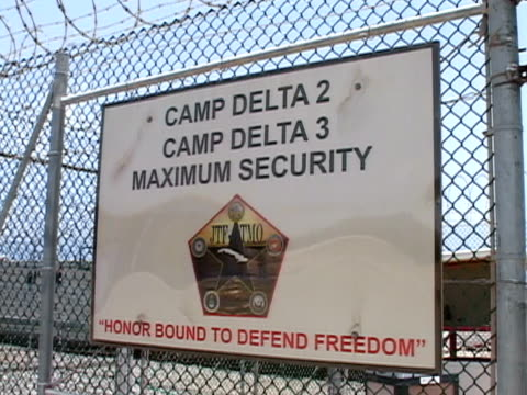 vídeos y material grabado en eventos de stock de closeup pan camp delta security sign hanging on fence at guantanamo bay detention center/ guantanamo province cuba - escritura occidental