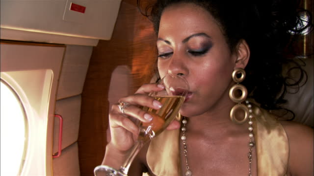 close-up pan diva smiling and drinking champagne on private airplane - bling bling stock-videos und b-roll-filmmaterial