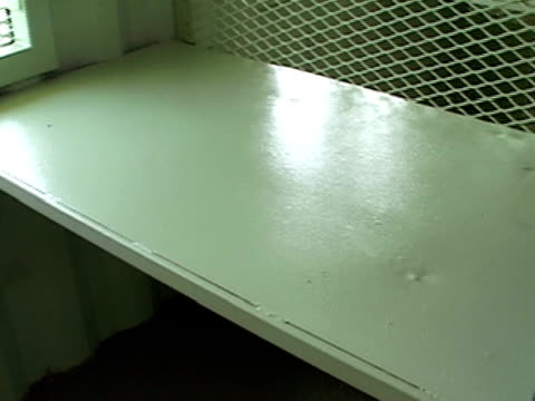 Closeup pan Folded mattress lying on metal cot in prison cell at Guantanamo Bay detention center/ Guantanamo Province Cuba