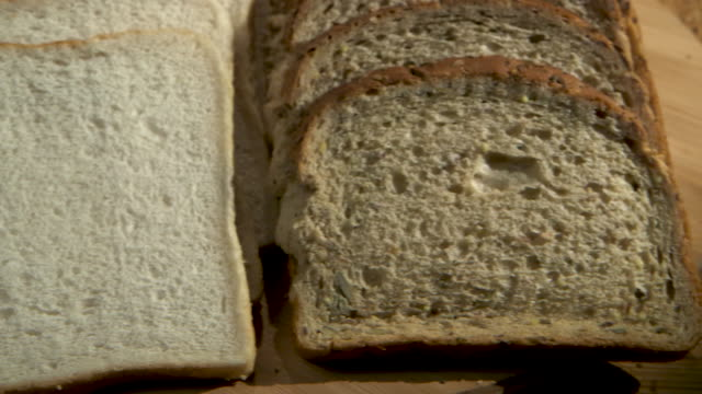 close-up pan left, then pan right over sliced white and brown seeded bread. - pane in cassetta video stock e b–roll