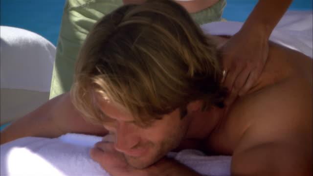 close-up pan masseuse massaging man at spa/ monterey county, california, usa - massagetisch stock-videos und b-roll-filmmaterial