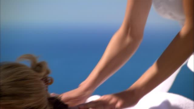 close-up pan masseuse massaging woman at spa/ monterey county, california, usa - massagetisch stock-videos und b-roll-filmmaterial
