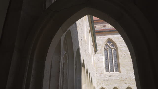 close-up pan of the arches in the courtyard arcade of an old german monastery, with stone carving, sandstone bricks, and bright reflected sunlight - erfurt, germany - stone object stock videos & royalty-free footage