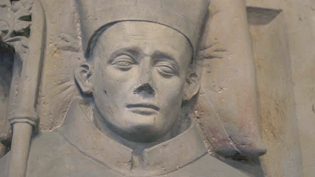 close-up pan of the face and crozier of a stone statue bishop in an old german church - erfurt, germany - 羊飼いの棒点の映像素材/bロール