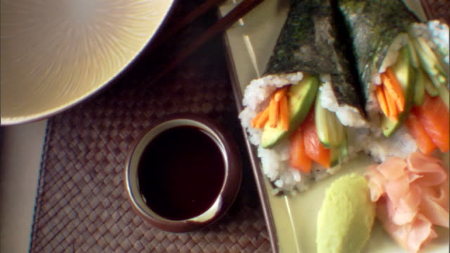 close-up pan right across a plate of cone sushi. - wasabi sauce stock videos and b-roll footage