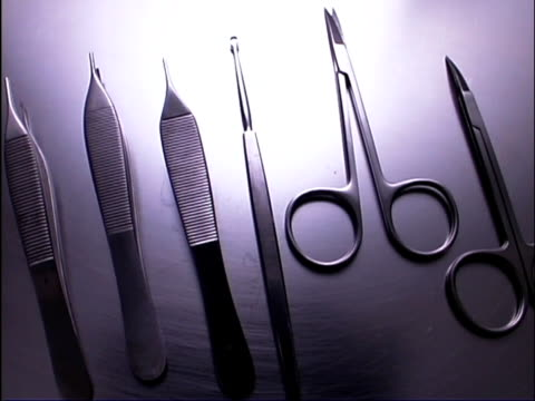 vidéos et rushes de close-up pan right arc of stainless steel tray of sterile surgical equipment. - groupe moyen d'objets