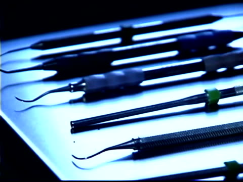 close-up pan right of dental instruments lying on a metal tray; blue tone. - medium group of objects stock videos & royalty-free footage